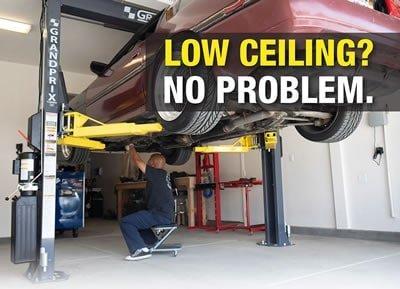 Mechanic using a chair to repair a car on a lift